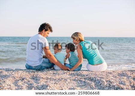 Family of four having fun on tropical beach - stock photo