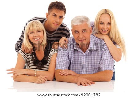 family of four in front of the white table portrait isolated on white background - stock photo