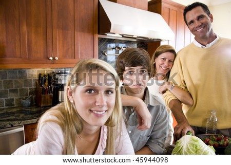 Family of four in kitchen, teenage boy frowning