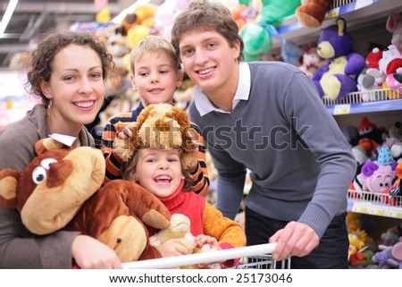Family of four in shop with soft toys, focus on little girl