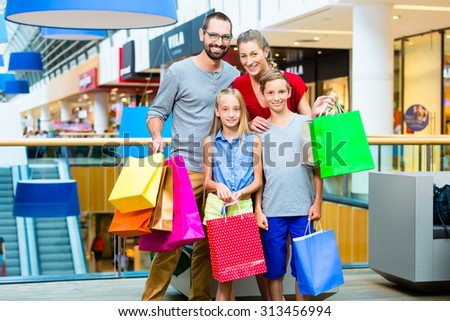 Family of four in shopping mall with bags - stock photo