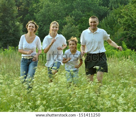 Family of four is having fun in a green summer park