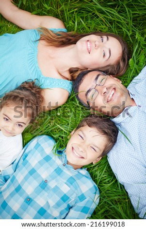 Family of four looking at camera with smiles while relaxing on grass - stock photo