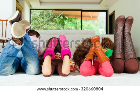 Family of four lying down facing away from camera with feet up in air. - stock photo