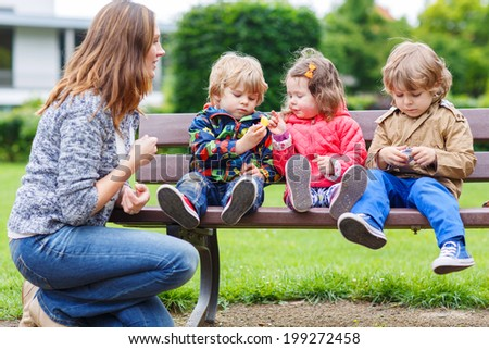 Family of four: Mother and her three children in summer park, two little boys and adorable girl - stock photo