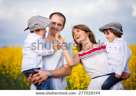 Family of four, mother, father and two boys,  in a oilseed rape field, laughing, smiling, hugging, giving a kiss, holding flowers - stock photo
