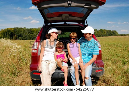 Family of four near their car on vacation - stock photo