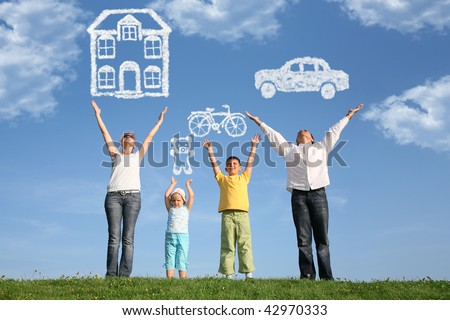 family of four on grass with hands up and dream - stock photo