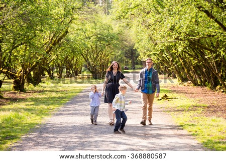 Family of four outdoors in a natural setting with nice light in a lifestyle portrait.