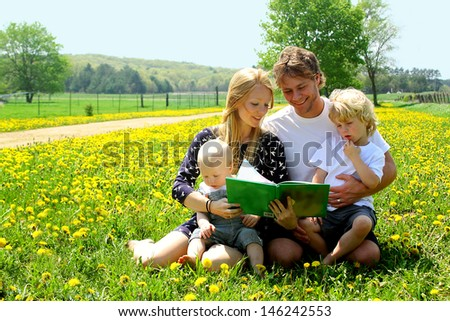 Family of four people including mother, father, baby, and little child are sitting outside in a field of dandelion flowers, reading a story
