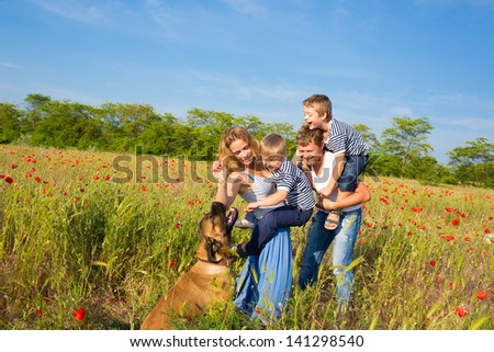 Family of four person and dog playing on the poppy field - stock photo