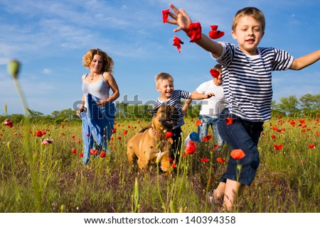 Family of four person playing on the poppy field - stock photo
