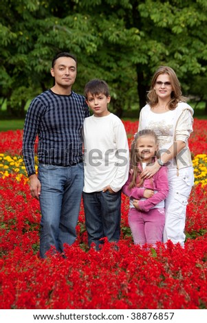family of four persons in flowering park - stock photo