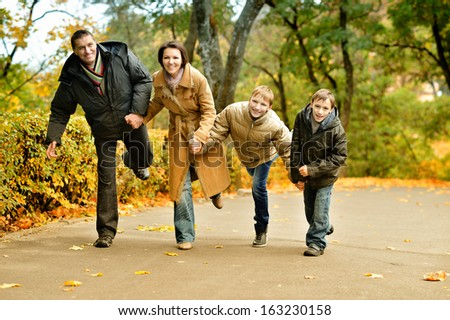 Family of four playing together in autumn forest