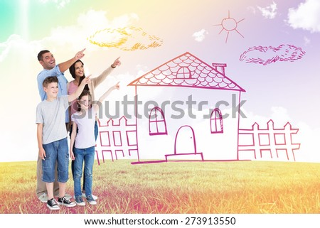 Family of four pointing at copy space against blue sky over green field - stock photo