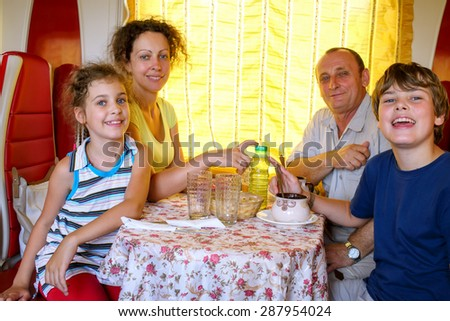 family of four posing at a table in the dining car of the train - stock photo