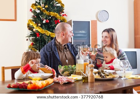Family of four posing for Christmas portrait around festive table at home