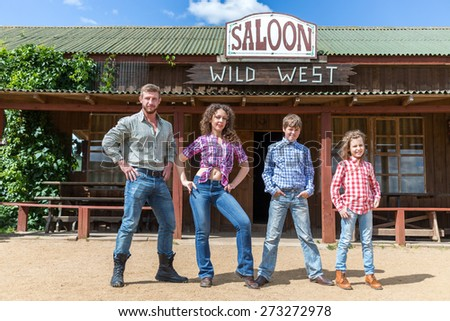 family of four posing on background of  wild west saloon - stock photo