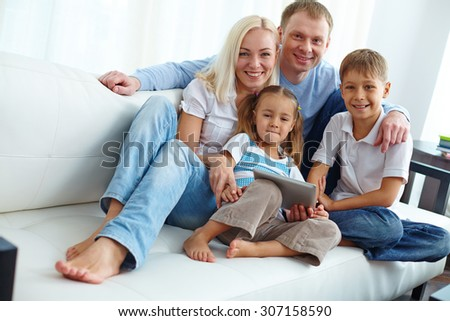 Family of four posing on sofa - stock photo