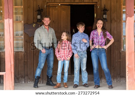 family of four posing on terrace of  wild west saloon - stock photo