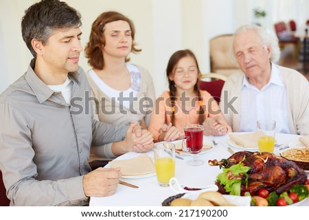 Family of four praying at festive table on Thanksgiving day, focus on young man - stock photo
