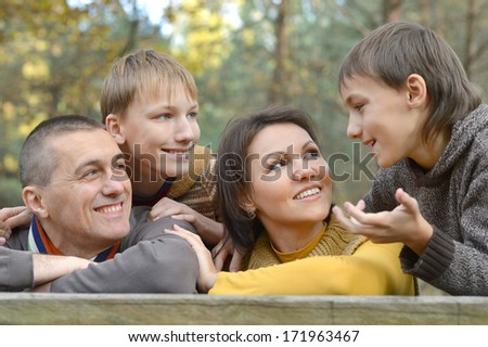 Family of four resting at table in autumn forest