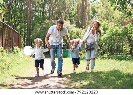 Family of four running on path outdoors at park with green grass and trees on background at sunny day / Young father, mother and two boys twins holding hands walking at countryside