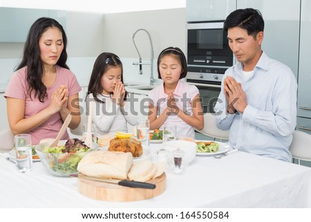 Family of four saying grace before meal in the kitchen at home - stock photo