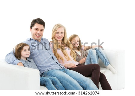 Family of four sitting on a sofa. Isolated on white background. - stock photo