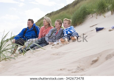 Family of four sitting on the sand dunes. They are wearing warm, casual clothing and looking out to sea.  - stock photo