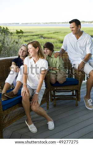 Family of four sitting together outdoors on terrace with view of Florida intercoastal waterway - stock photo