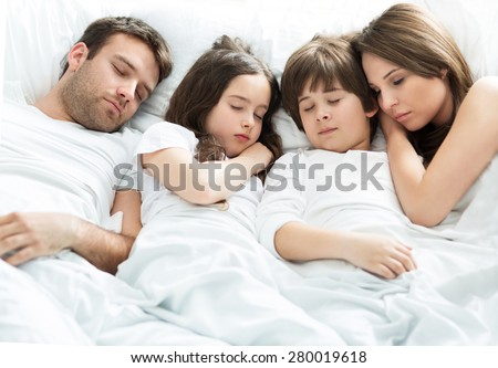 Family of four sleeping  - stock photo