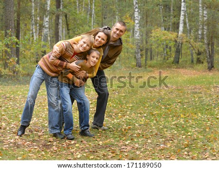 Family of four spending time in autumn forest - stock photo