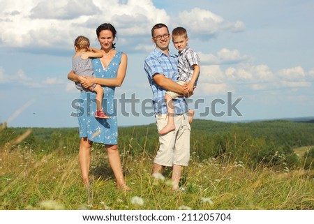 Family of four standing on a mountain on the background of clouds. Portrait of a happy family.