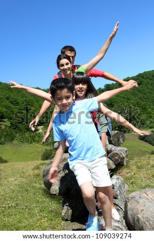 Family of four standing on rocks in the mountain - stock photo