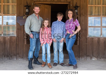 family of four standing on terrace of  wild west saloon - stock photo