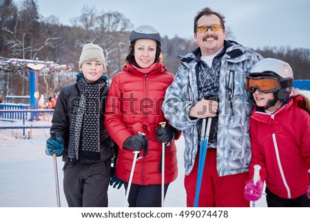 Family of four stands on skis at ski resort in evening.