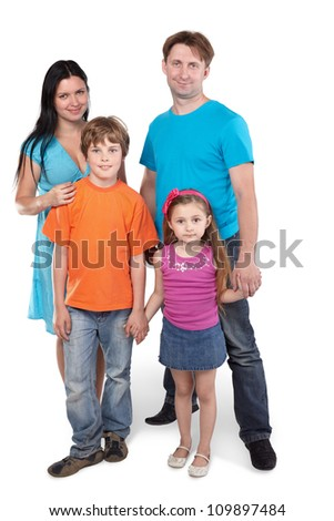 Family of four stands together holding hands - stock photo
