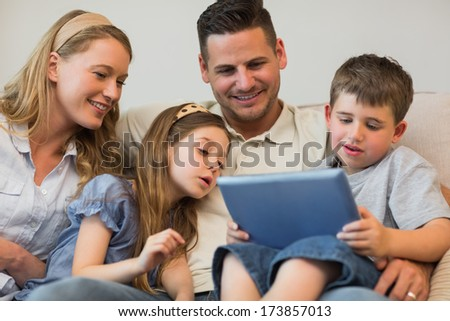 Family of four using digital tablet together on sofa at home