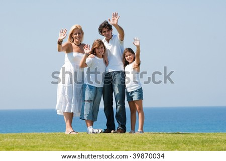 Family of four waving at camera - stock photo