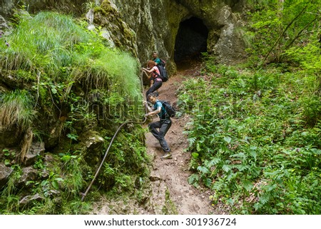 Family of hikers getting out from a cave holding on to a safety cable