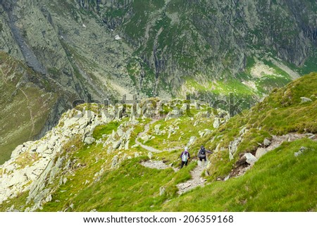 Family of hikers on a trail in the Fagaras mountains in Romania - stock photo