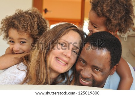 Family of mixed race play together on a bed - stock photo