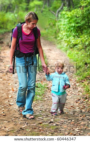 family of mother and baby walking in the forest - stock photo