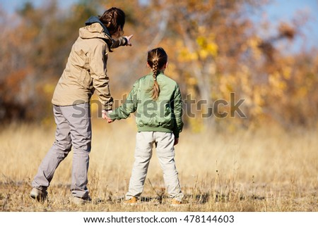 Family of mother and child on African safari vacation enjoying bush view