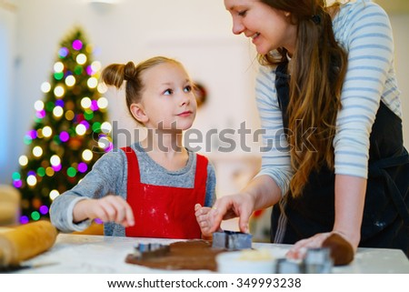 Family of mother and daughter baking cookies at home on Xmas eve. Beautifully decorated room, fireplace, Christmas tree and lights on background. - stock photo