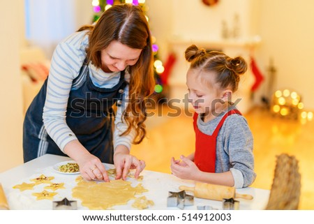 Family of mother and daughter baking cookies at home on Xmas eve. Beautifully decorated room, fireplace, Christmas tree and lights on background.