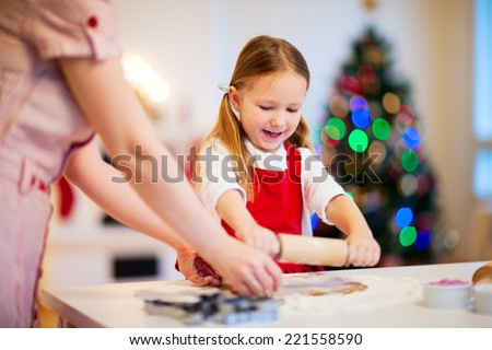 Family of mother and daughter baking gingerbread cookies at home on Christmas eve - stock photo