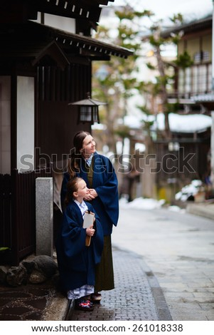 Family of mother and daughter wearing yukata traditional Japanese kimono at street of onsen resort town in Japan going to public hot spring spa. - stock photo