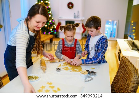Family of mother and kids baking cookies at home on Xmas eve. Beautifully decorated room, Christmas tree and lights on background.